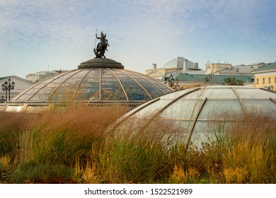 Moscow, Russia - October 3, 2019: Manezhnaya Square. Glass domes of an underground shopping center with a Monument of holy patron of Moscow George Victorious and Dragon, in the autumn grass.
