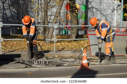 MOSCOW, RUSSIA - OKTOBER, 2012: Dump truck with dismantled asphalt and a worker in an orange overalls with a jackhammer  in Moscow.
