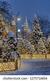 MOSCOW, RUSSIA - Old style street lamp with clock  framed with the beautiful and festive illuminated Christmas trees on Manezhnaya square in background of towers of Moscow Kremlin in morning twilight.