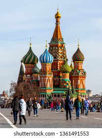 MOSCOW, RUSSIA, on April 4, 2019. People walk at Red Square at walls of the Moscow Kremlin. St. Basil's Cathedral in the distance