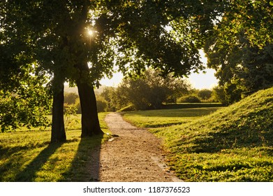 """MOSCOW, RUSSIA - On a Walking Path Against Beams of the Autumn Sun. Beautiful autumn landscape in Moscow park and museum-preserve """"Kolomenskoye"""" (former royal residence)."""