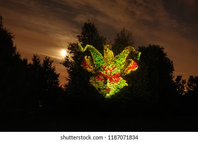 """MOSCOW, RUSSIA - Sept 23, 2018 Jester Mask Under Moonlight. Revived mask of a court jester projected on a tree during light show of Moscow International Festival """"Circle of Light"""" in Kolomenskoye."""