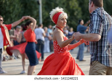 Moscow, Russia, September 08, 2018: a woman in adulthood in a stylish red dress and with a red bandage on her blonde hair dancing on the dance floor in Gorky Park