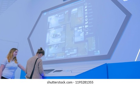 MOSCOW, RUSSIA - SEPTEMBER 10, 2017: Smart City Exhibition. Woman using interactive touchscreen console in front of large display at urban exhibition. Education and technology concept