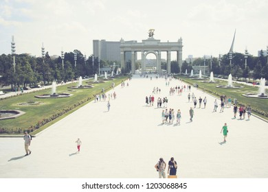 MOSCOW, RUSSIA - SEPTEMBER 10, 2018: Panoramic view of the Arch of the Main Entrance of VDNKh and walking people in sunny weather in Moscow.