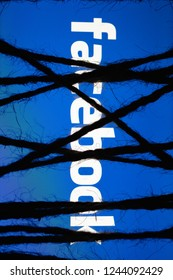 """MOSCOW, RUSSIA - September 14, 2018: Smartphone in the dark, tightly wrapped and tied with coarse jute rope bondage lies with a glowing blue screen with white text """"facebook"""". Concept of censorship"""