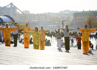 Moscow, Russia, September 15, 2018: people in yellow suits engaged in recreational gymnastics qigong in an urban environment