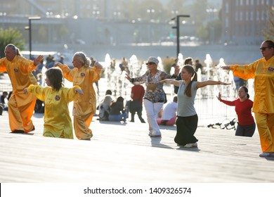Moscow, Russia, September 15, 2018: young and old people and people in yellow suits are engaged in health gymnastics qigong in the urban environment