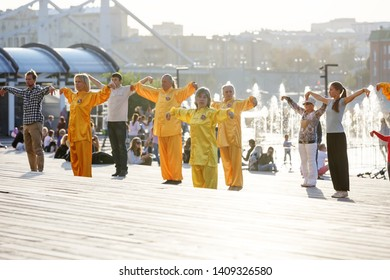 Moscow, Russia, September 15, 2018: young and old people and people in yellow suits are engaged in health gymnastics qigong in the urban environment on the Crimean embankment