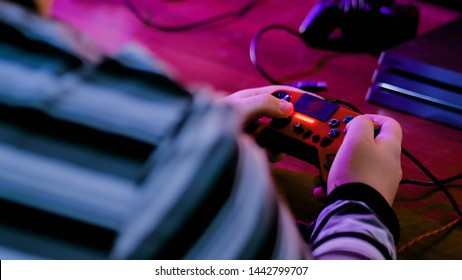 MOSCOW, RUSSIA - SEPTEMBER 16, 2018: ESports Cup - Man playing video game with Sony Dualshock controller for PlayStation. Gaming, esport and cybersport concept