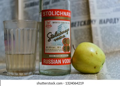 """Moscow / Russia - September 20 2018:  Stress relief technique for Russians. Vodka Stolichnaya, green apple, glass with old soviet newspaper """"Pravda"""". Translation of the newspaper name is the """"Truth"""""""