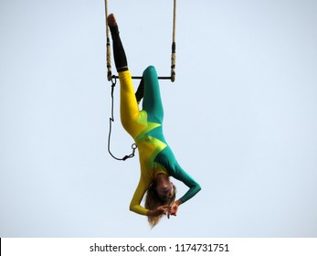 """Moscow, Russia - September 2018: Aerial gymnast girl hanging upside down on trapeze isolated on sky background during a performance """"Mobile Homme"""" on the day of Moscow. Acrobat woman"""