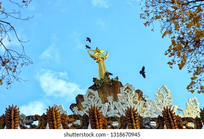 """MOSCOW, RUSSIA - SEPTEMBER, 2018: The crows ominously circle over the spire. Pavilion №58 """"Agriculture"""" """"Ukrainian SSR"""", at the All-Russia Exhibition Center, VVC."""