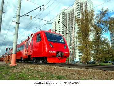 MOSCOW, RUSSIA - SEPTEMBER, 2018: The electric train quickly rushes past residential buildings.