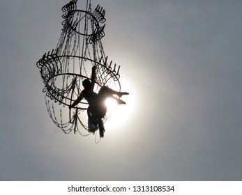 Moscow, Russia - September 2018: Silhouette of girl aerial gymnast hanging on chandelier against the sun shining. Acrobat woman during a street circus performance