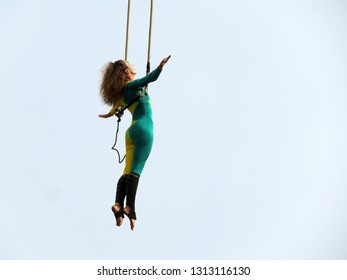 Moscow, Russia - September 2018: Woman aerial acrobat hanging on trapeze isolated on sky background during a performance of french circus Les Tambours. Girl gymnast during a street show