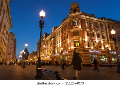Moscow, Russia - September 21, 2017: People and historical building decorated by warm light at Arbat walking street during twilight with blue sky.