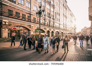 Moscow, Russia - September 21, 2017: People walking around crowded Arbat street with scene of sunlight behind historic building.