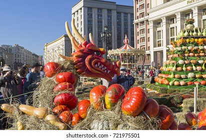 """MOSCOW, RUSSIA - SEPTEMBER 22, 2017:  Figure of fairy-tale dragons made of ripe orange pumpkins on Manege Square near the Four Seasons Hotel. Festival """"Golden Autumn"""", Moscow, Russia. September 2017."""