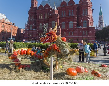 """MOSCOW, RUSSIA - SEPTEMBER 22, 2017: Fairy dragon made of ripe orange pumpkins against the backdrop of the building of the Historical Museum. Festival """"Golden Autumn"""", Moscow, Russia. September 2017"""