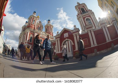 Moscow, Russia - September 23 2019: Temple of the Holy Martyr Clement, Pope in Moscow Zamoskvorechye. People hurry up in sunny autumn day. Pair of young man and woman hurrying up. Fish-Eye lens.