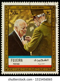 """Moscow, Russia - September 26, 2019: A stamp printed in Fujeira shows General Charles de Gaulle and Winston Churchill in 1958, series """"Charles de Gaulle"""", circa 1972"""