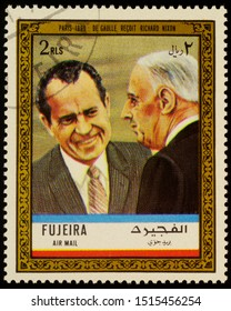 """Moscow, Russia - September 26, 2019: A stamp printed in Fujeira shows President de Gaulle receives Richard Nixon in Paris in 1969, series """"Charles de Gaulle"""", circa 1972"""