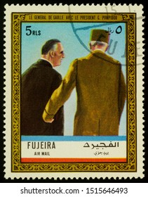 """Moscow, Russia - September 26, 2019: A stamp printed in Fujeira shows General Charles de Gaulle walking with President Georges Pompidou, series """"Charles de Gaulle"""", circa 1972"""