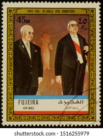 """Moscow, Russia - September 28, 2019: A stamp printed in Fujeira shows President Charles de Gaulle with Soviet leader Nikita Khroutchev in Paris in 1960, series """"Charles de Gaulle"""", circa 1972"""