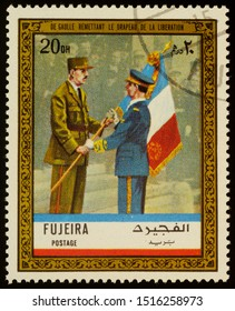 """Moscow, Russia - September 28, 2019: A stamp printed in Fujeira shows General Charles de Gaulle with French flag, series """"Charles de Gaulle"""", circa 1972"""