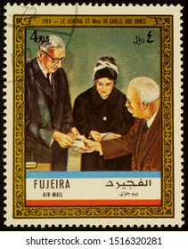 """Moscow, Russia - September 28, 2019: A stamp printed in Fujeira shows Charles de Gaulle and his wife at voting in 1969, series """"Charles de Gaulle"""", circa 1972"""