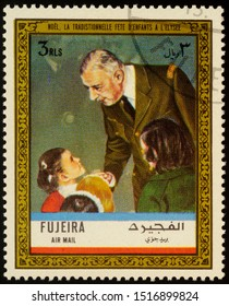 """Moscow, Russia - September 28, 2019: A stamp printed in Fujeira shows Charles de Gaulle with children on Christmas, traditional children's party at the Elysee, series """"Charles de Gaulle"""", circa 1972"""