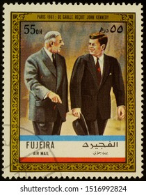 """Moscow, Russia - September 28, 2019: A stamp printed in Fujeira shows President Charles De Gaulle receives John Kennedy in Paris in 1961, series """"Charles de Gaulle"""", circa 1972"""