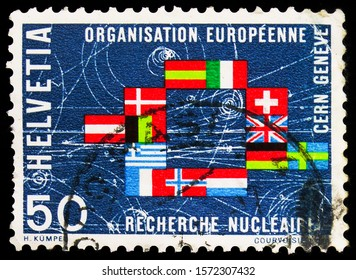 MOSCOW, RUSSIA - SEPTEMBER 30, 2019: Postage stamp printed in Switzerland shows Nuclear fission phase & flags of participating countries, C.E.R.N. serie, circa 1966