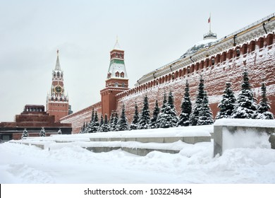 MOSCOW, RUSSIA - Snow-covered blue pine trees along the Kremlin wall and towers, Lenin Mausoleum and Spasskaya Tower at Red Square during heavy snowfall of the century.