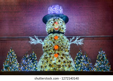 MOSCOW, RUSSIA - Snowman in Hat with Christmas Trees at the Wall of the Power Plant No 1,the fragment of New Year decorations at Raushskaya Embankment on the first night of 2019 New Year.