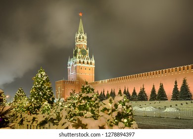 MOSCOW, RUSSIA - Spasskaya (Savior's) Tower of Moscow Kremlin Framed by Christmas Trees in Snow at Night. Beautiful view on one of the most well known Russian  landmarks at the Red Square.
