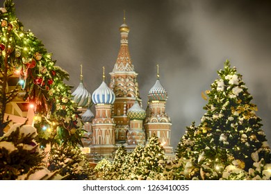MOSCOW, RUSSIA - St. Basil's Cathedral Framed by Christmas Trees in Snow at Night. The winterholiday postcard from Red Square under snowfall.