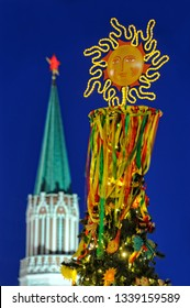 MOSCOW, RUSSIA - The topper of a fir tree in form of smiling sun with colorful ribbons in background of Nikolskaya tower of Moscow Kremlin on Manezhnaya square in twilight.