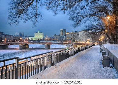 MOSCOW, RUSSIA - Twilight view of frozen Moskva River, Borodino Bridge (Borodinsky Most), House of Government of Russian Federation (White House) from a small park at 7th Rostovskiy lane.