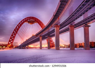 MOSCOW, RUSSIA - Under Zhivopisny Bridge Curve in Winter Twilight. View from an ice on the river Moskva (Moscow) at the bank near Karamyshevsky passage on the highest in Europe cable-stayed bridge.