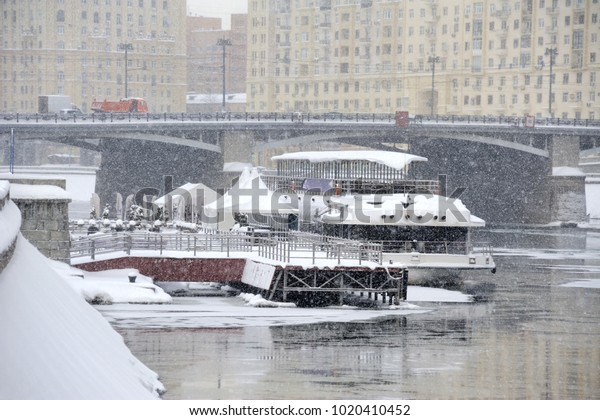 """MOSCOW, RUSSIA - View from Berezhkovskaya embankment on a riverboat at pier """"Kievskaya"""" in Moskva (Moscow) River under a heavy snowfall of the century at the begining of February 2018"""