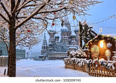 MOSCOW, RUSSIA - View from corner of Christmas market at Red Square on St. Basil's Cathedral, framed by a tree decorated with festive new year balls after heavy snowfall in the early winter morning.