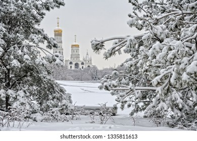 MOSCOW, RUSSIA - View from the covered snow Zaryadye park on the Ivan the Great Bell Tower of Moscow Kremlin framed by white spruce trees. Beautiful Moscow winter cityscape in a heavy snowfall.