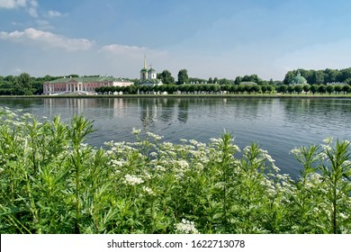 MOSCOW, RUSSIA - View from opposite side of Grand Pond on the architectural ensemble of Kuskovo Estate, the Grand Summer Palace, the Church of Our Savior Of The All-Merciful, trimmed alley of trees