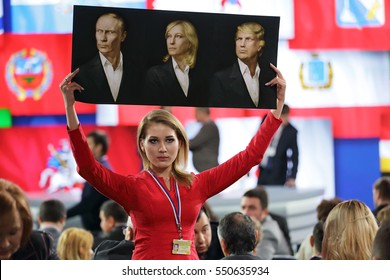 MOSCOW, RUSSIA-DEC 23, 2016: An activist of the NLM Katasonova Maria holds a poster with the image of Vladimir Putin, Marine Le Pen, and Donald Trump at the press conference of the President of Russia
