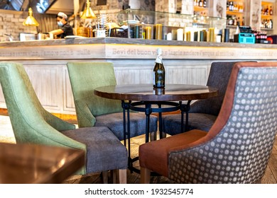 Moscow Russia-march 2021:A bottle of wine on an empty table Surrounded by cozy armchairs against the backdrop of the kitchen area. Italian restaurant interior.