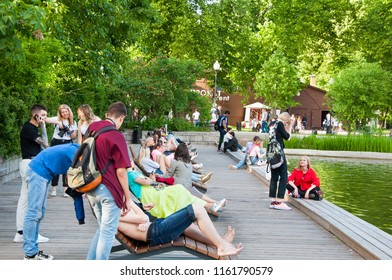Moscow, Russia-May27,2018: Crowd of locals relax in Neskuchny Garden around Golitsyn (large) pond during midday.