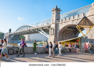 Moscow, Russia-May27,2018: Pushkin embankment full of people around Neskuchny Garden with Pushkin (Andreevsky) pedestrian bridge across Moscow river.