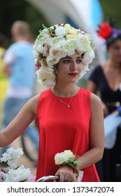 "MOSCOW, RUSSIAN FEDERATION - AUGUST 7, 2016: Woman in unusual dress, accessories and hat with flowers, participant of cycle parade ""Lady on bicycle"" in Gorky Park (free access, without tickets)."